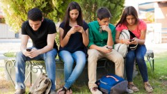Group of teenage boys and girls ignoring each other while using their cell phones at school )(shutterstock