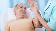 (senior with painful arm during rehabilitation (shutterstock