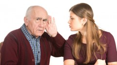 young woman makes hearing test for old senior (man (shutterstock